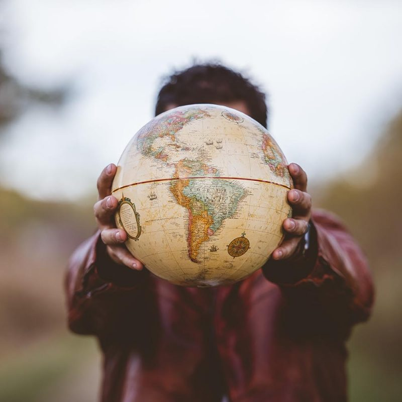 A closeup shot of a male wearing a leather jacket holding a globe in front of him with a blurred background